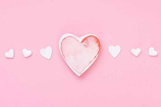 Arranjo de vista superior com biscoitos em forma de coração e fundo rosa Foto gratuita