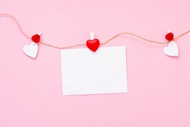 Arranjo de vista superior com corações e pedaço de papel Foto gratuita