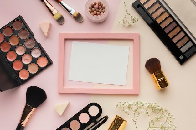 Arranjo de vista superior com cosméticos e moldura rosa Foto gratuita