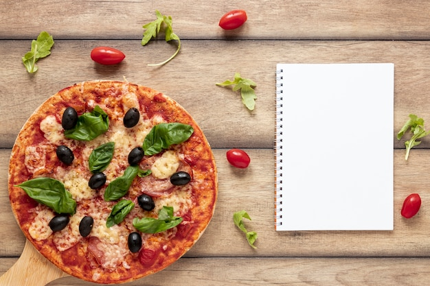 Arranjo de vista superior com pizza e notebook Foto gratuita