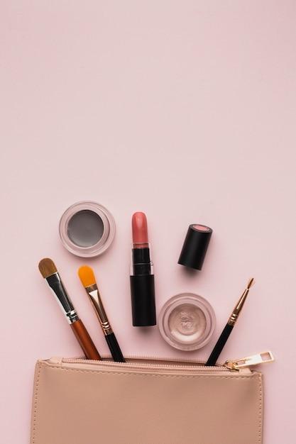 Arranjo de vista superior com produtos de maquiagem com bolsa de beleza Foto gratuita