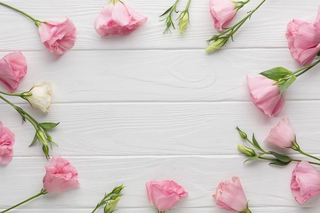 Arranjo de vista superior com rosas rosa em fundo de madeira Foto gratuita