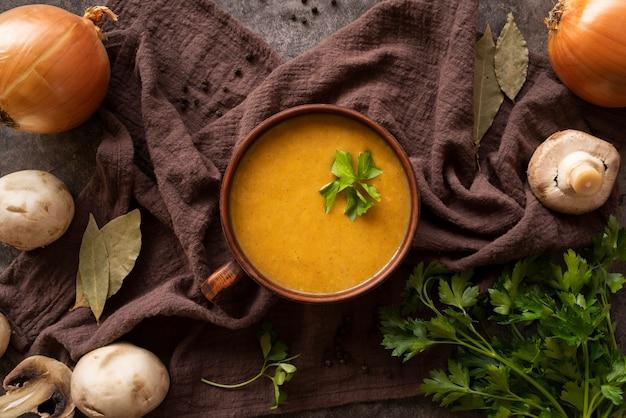 Arranjo de vista superior com sopa de abóbora e cogumelos Foto gratuita