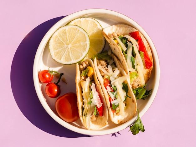 Arranjo liso leigo com comida deliciosa no fundo roxo Foto gratuita