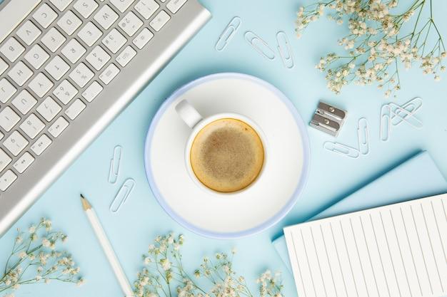 Arranjo no local de trabalho em fundo azul com uma xícara de café Foto gratuita