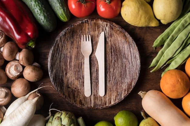 Arranjo plano de legumes com prato Foto gratuita