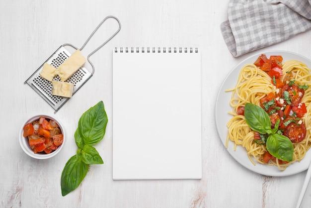 Arranjo plano de refeição de comida local com bloco de notas Foto gratuita