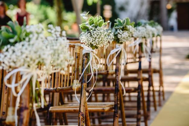 Arranjos florais para cadeiras vazias para uma cerimônia de casamento na primavera Foto Premium