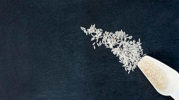 Arroz branco em uma colher na mesa preta Foto gratuita