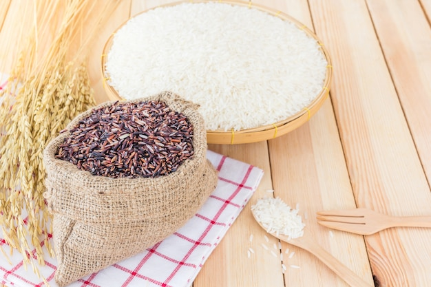 Arroz branco jasmim tailandês e arroz riceberry em cesta de bambu e saco em fundo de madeira Foto Premium