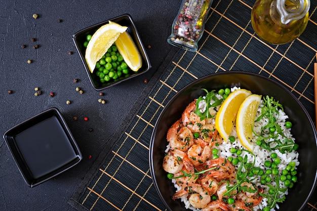 Arroz com jovens ervilhas, camarões e rúcula em tigela preta. comida saudável. tigela de buda. vista do topo. configuração plana Foto gratuita