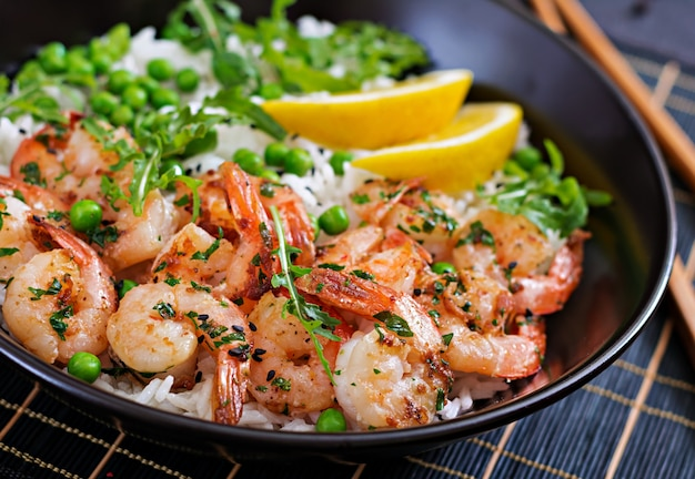 Arroz com jovens ervilhas, camarões e rúcula em tigela preta. comida saudável. tigela de buda Foto gratuita