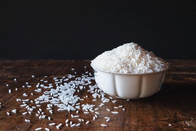 Arroz cru branco em uma tigela sobre uma mesa de madeira Foto Premium