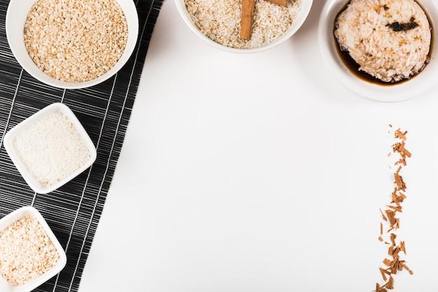 Arroz cru em placemat e arroz de molho de soja no fundo branco Foto gratuita