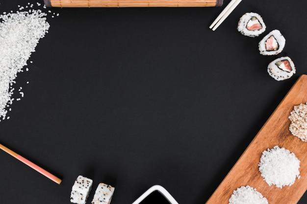 Arroz cru; pauzinhos; molho de sushi e soja em fundo preto Foto gratuita
