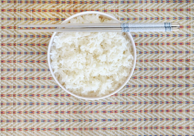 Arroz em tigela branca com pauzinho Foto Premium