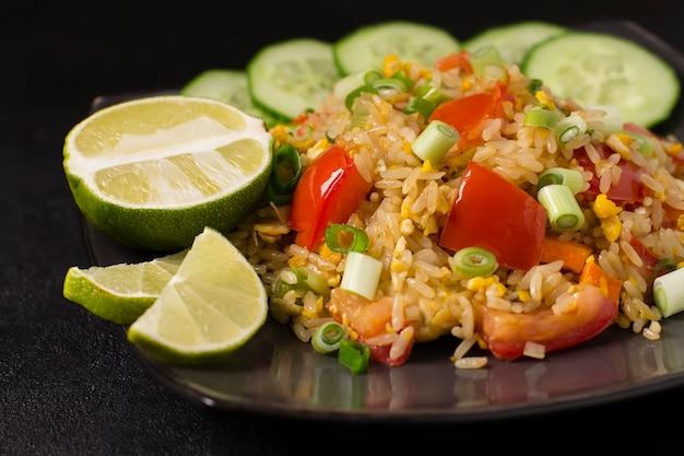 Arroz frito com khao pad kung asiático com vegetais, carne, ovo, pepino fresco e tomate Foto Premium