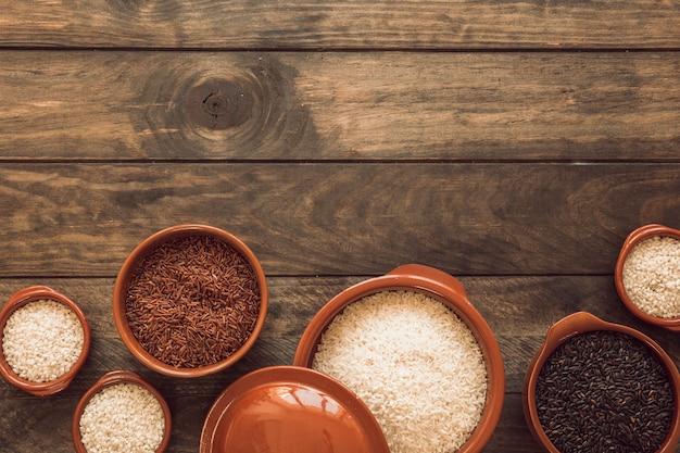 Arroz integral de jasmim marrom; arroz branco e arroz orgânico na tigela na mesa de madeira Foto gratuita