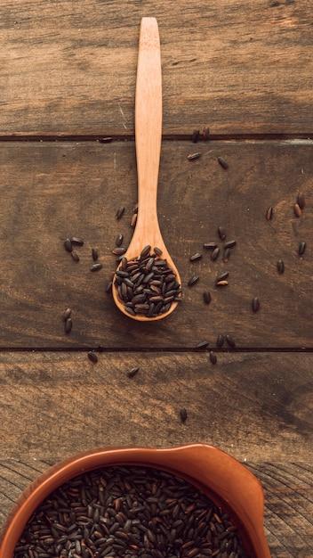 Arroz orgânico marrom na colher de pau e tigela na mesa de madeira Foto gratuita