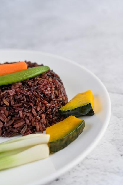 Arroz preto em um prato com abóbora, ervilha, cenoura, milho de bebê Foto gratuita