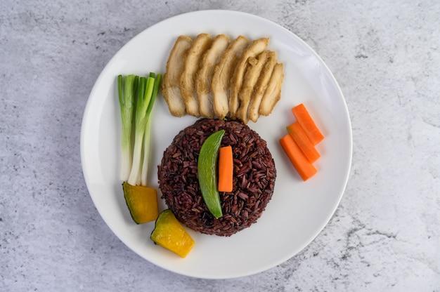 Arroz preto em um prato com abóbora, ervilhas, cenouras, milho e peito de frango cozido no vapor. Foto gratuita