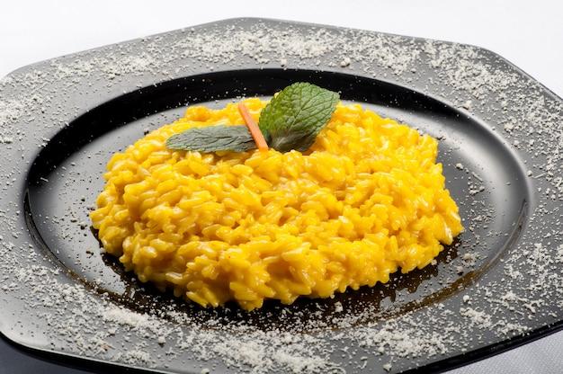 Arroz risotto amarelo guarnecido com cenoura e hortelã Foto Premium