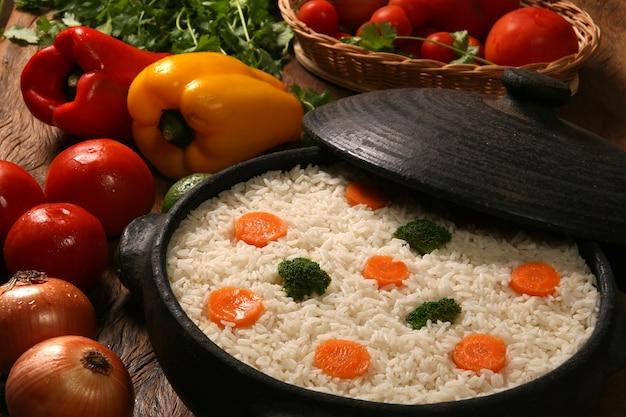 Arroz saudável apetitoso com legumes em chapa branca sobre uma mesa de madeira. arroz colorido Foto Premium