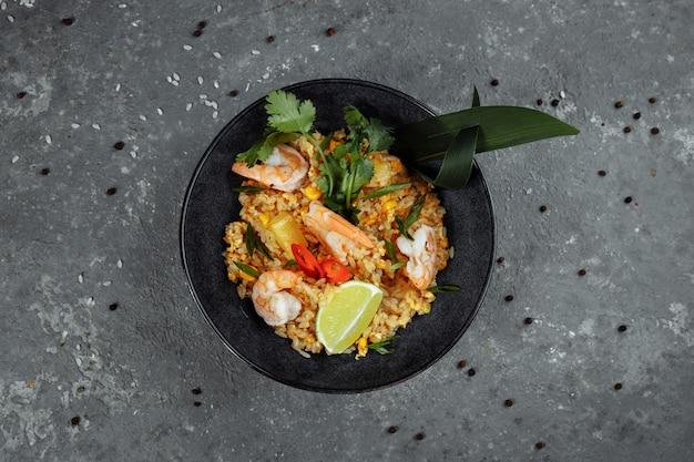Arroz tailandês com camarão em uma placa preta em um fundo escuro. local dos direitos autorais Foto Premium