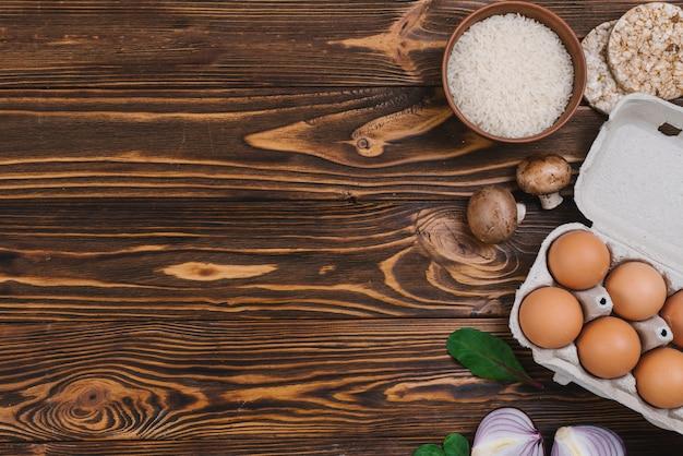 Arroz tufado; grãos de arroz; cogumelo; ovos e cebola sobre a mesa de madeira Foto gratuita