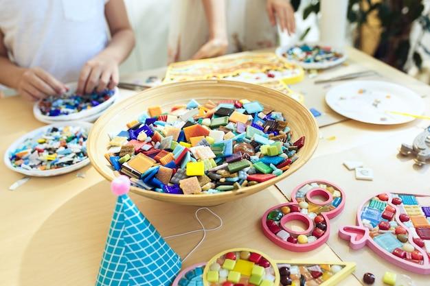 Arte de quebra-cabeça de mosaico para crianças, jogo criativo infantil. mãos estão jogando mosaico na mesa. detalhes coloridos multicoloridos close-up. Foto gratuita