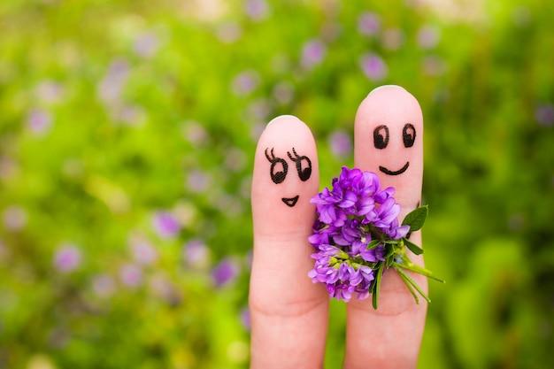 Arte do dedo de um casal feliz. homem está dando flores para uma mulher. Foto Premium