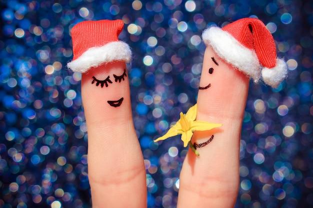 Arte do dedo do casal feliz. o homem está dando flores para a mulher Foto Premium