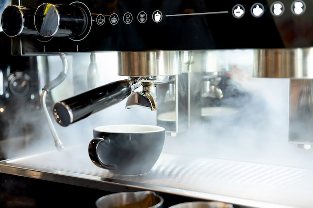 Arte do latte do copo de café colocada no vapor da máquina da cafeteira no café da cafetaria Foto Premium