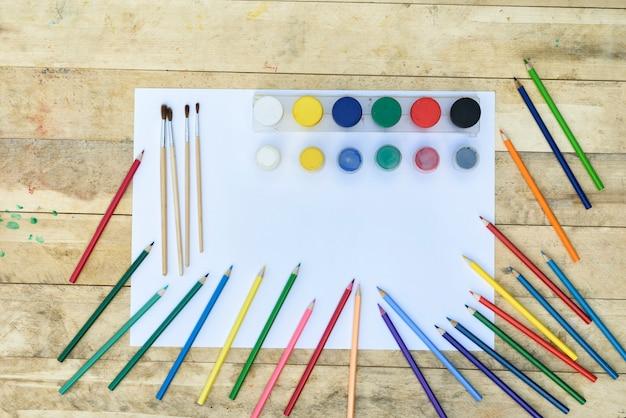 Arte . muitos lápis de cor, pincéis e potes de tinta em uma folha de papel em branco. mesa de madeira Foto Premium