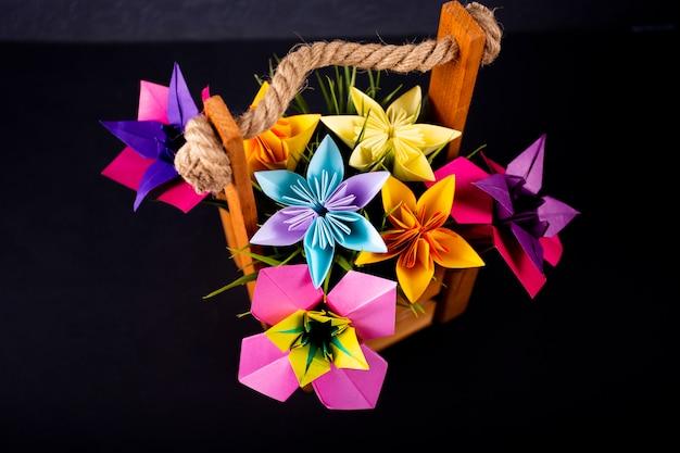 Artesanal colorido papel flores origami buquê papel artesanato arte em uma cesta com grama no estúdio no darkbackground Foto Premium
