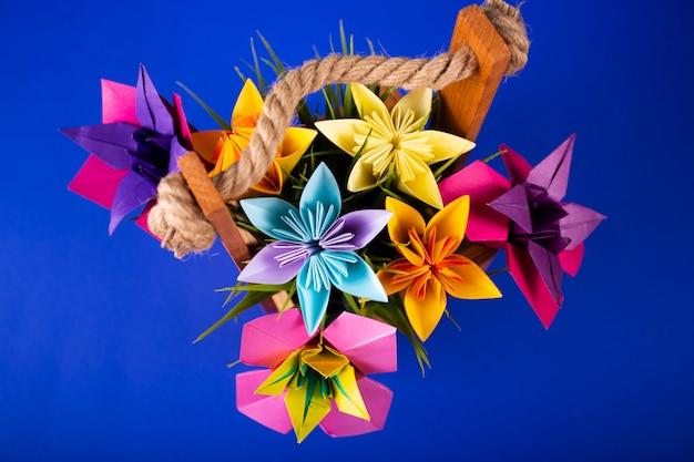 Artesanal de flores de papel colorido origami buquê de papel ofício arte em uma cesta com grama no estúdio em fundo colorido topshot Foto Premium