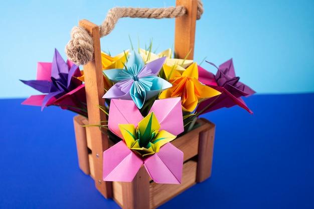 Artesanal flores de papel colorido origami buquê de papel ofício arte em uma cesta com grama no estúdio em plano de fundo colorido closeup Foto Premium