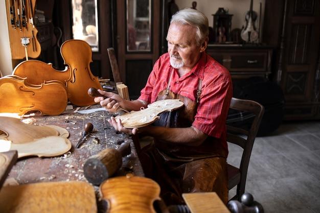 Artesão carpinteiro sênior esculpindo madeira e fazendo violino Foto gratuita