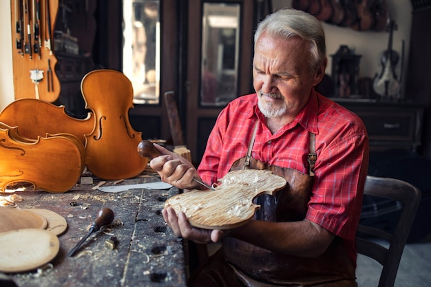 Artesão carpinteiro sênior esculpindo madeira em sua oficina antiquada Foto gratuita
