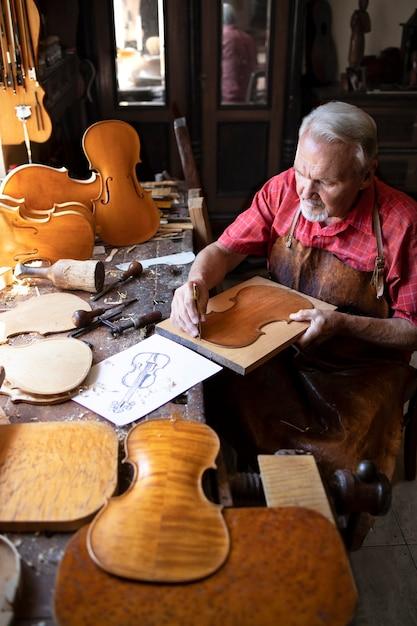 Artesão carpinteiro sênior fazendo violino em sua antiga oficina de carpinteiro Foto gratuita