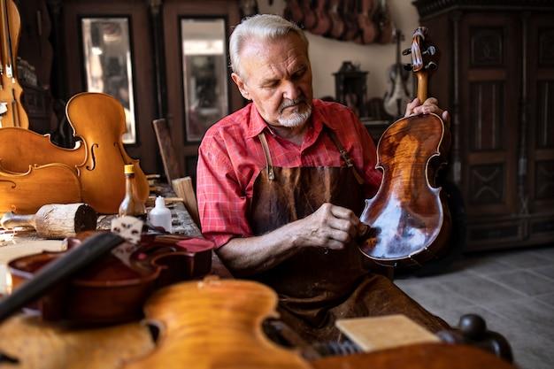 Artesão carpinteiro sênior polindo instrumento de violino em sua oficina de carpinteiro Foto gratuita