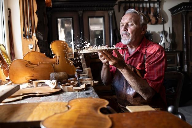 Artesão carpinteiro sênior trabalhando com madeira nobre na oficina e soprando serragem Foto gratuita