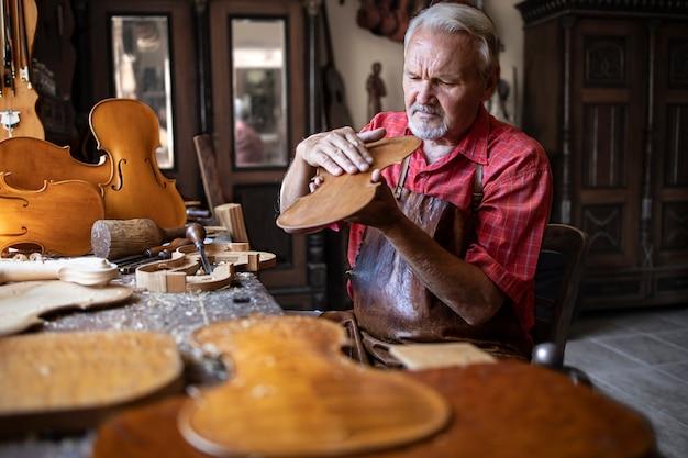 Artesão carpinteiro sênior verificando a qualidade do produto de madeira Foto gratuita
