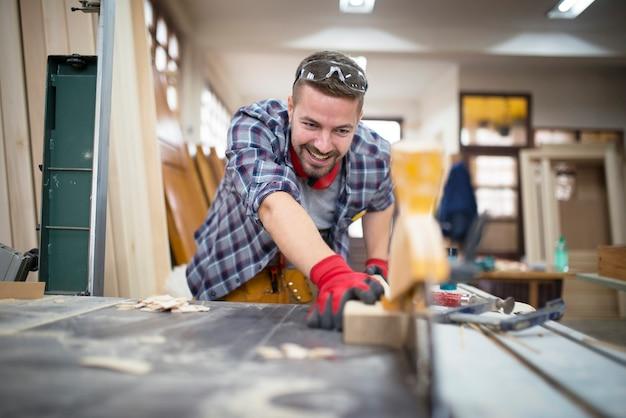 Artesão sorridente profissional cortando planta em máquina circular em oficina de carpintaria para trabalhar madeira Foto gratuita