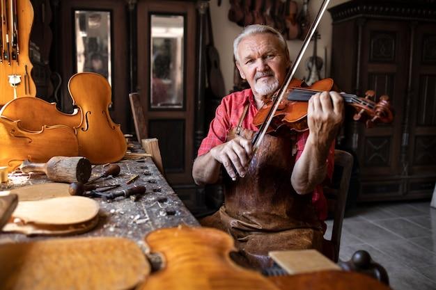 Artesão verificando a qualidade e tocando violino em sua antiga oficina de carpinteiro Foto gratuita