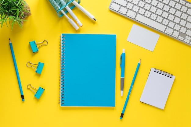 Artigos de papelaria azuis com teclado e bloco de notas em espiral no pano de fundo amarelo Foto gratuita