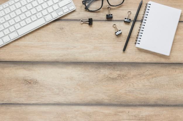 Artigos de papelaria colocados perto de teclado e óculos na mesa de madeira Foto gratuita
