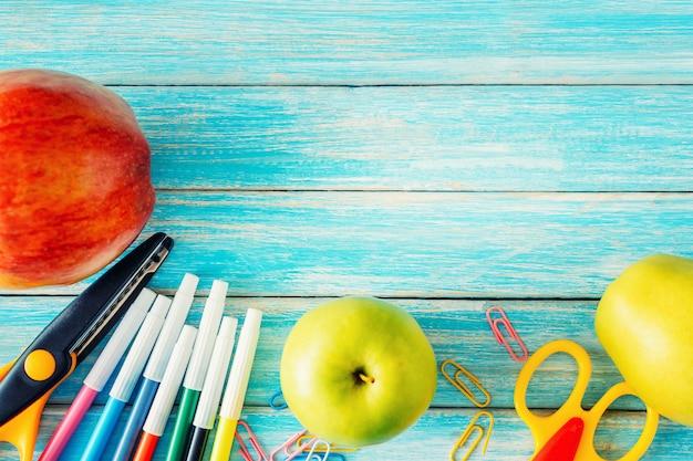 Artigos de papelaria da escola, ferramentas de escritório e maçãs na vista superior azul de madeira nackground Foto Premium