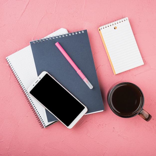 Artigos de papelaria do escritório com uma xícara de café Foto gratuita
