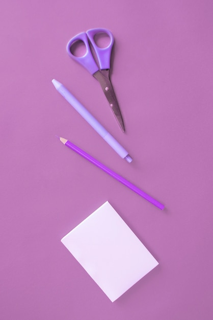 Artigos de papelaria do escritório na superfície roxa Foto gratuita